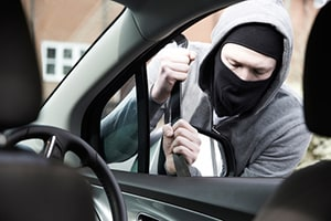 Masked Man Breaking Into Car With Crowbar